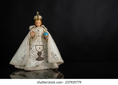 Infant Jesus of Prague in white vestments on a dark background