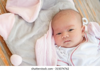infant lies in a small baby bed and soft material on wooden floor