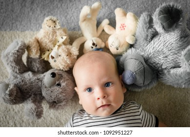 The infant lies surrounded by teddy bears