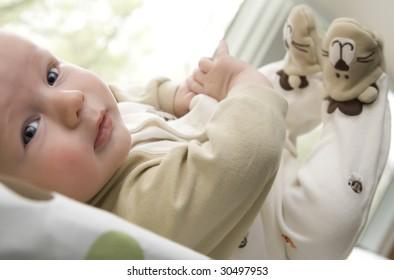 Infant lying down with feet up in the air