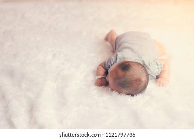 Infant newborn baby lying donw on bed. little kid pure and innocent.