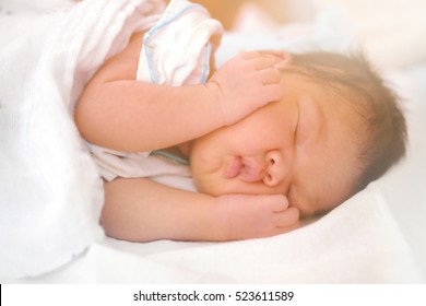 infant on the white mattress and catching her face with orange light