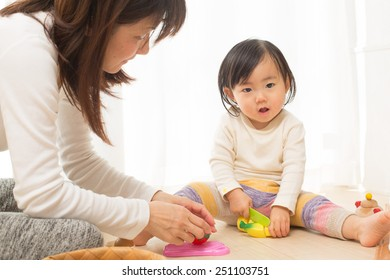 infant plays with mom