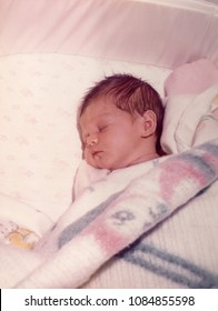 Infant sleeping in a crib with pink and blue and white blanket