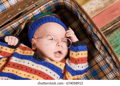 Infant in spectacles. Small child with opened mouth.