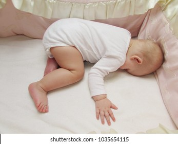 the infant in white clothes is sleeping, lying on his stomach, in his white crib. baby is sleeping face down