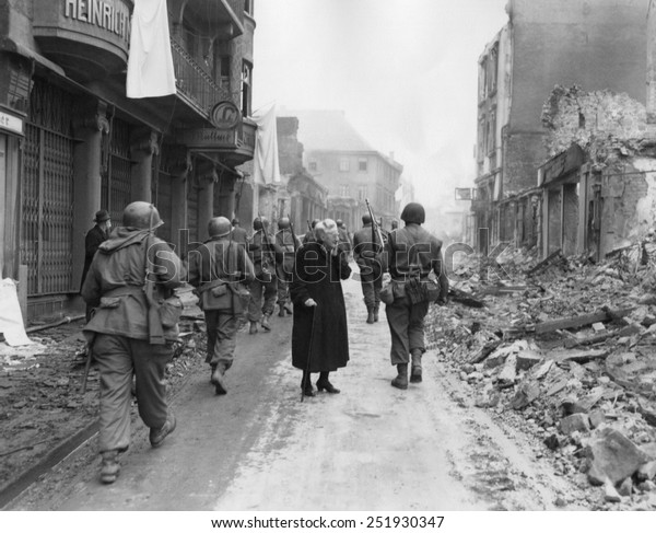 As infantrymen march through a German town, a shocked old woman stares at a the ruins. March-April 1945. Germany, World War 2.