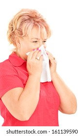 Infected mature woman blowing her nose in tissue paper because of being ill isolated on white background