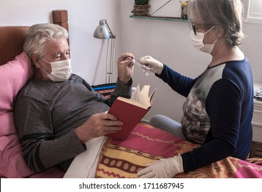 Infection coronavirus . Senior couple with man sick by covid-19 lying down in bed at home wearing medical mask. Quarantine self isolation concept