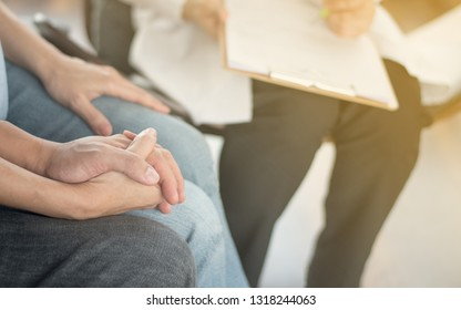 Infertility problem with marriage couple IVF concept. A fertility doctor or reproductive endocrinologist with man and women holding hand together in therapy consult session of inability to pregnant.
