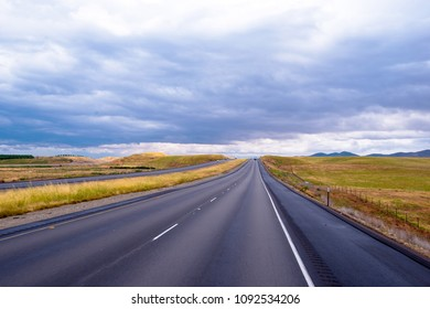 Infinite smooth straight divided interstate multiline highway road with markings and car leaving the horizon in the middle of the summer yellow meadows of California on the clouds background