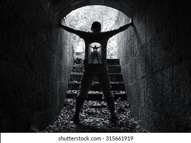 Infinity inner world concept, young man stands in dark stone tunnel with glowing end