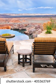 Infinity pool and patio lounge chairs with a view of an endless desert landscape. Location: Arizona, USA