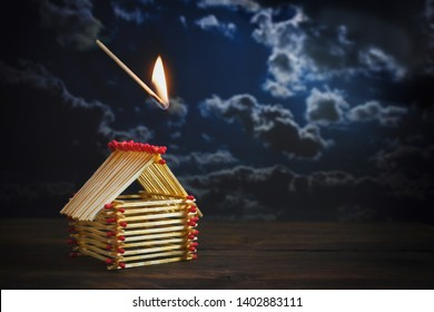 inflamed match is falling on a house built of matches against a dark stormy sky with copy space, insurance concept