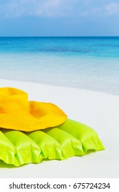 Inflatable air swim mattress and summer hat on sandy coastline close to turquoise sea, beach summer accessories.