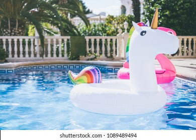 Inflatable colorful white unicorn at the swimming pool. Fun time in the Summer at swimming pool. concept