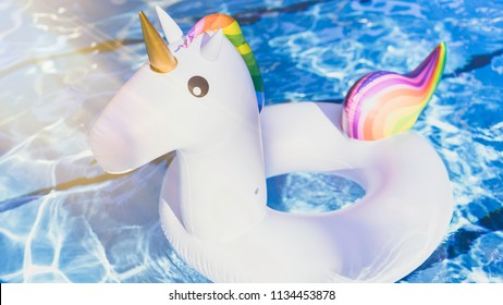 Inflatable colorful white unicorn at the swimming pool. Vacation time in the swim pool with plastic toys. Relaxation concept. Ripple Water in swimming pool with sun reflection.Sunlights effects