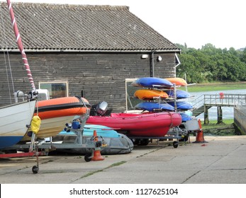 Inflatable dinghy and kayaks at the boathouse by the river.