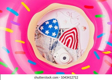 Inflatable donut float, American flag crochet bikini, camera and shorts. Summer vacation holiday concept, flat lay, vibrant colors.