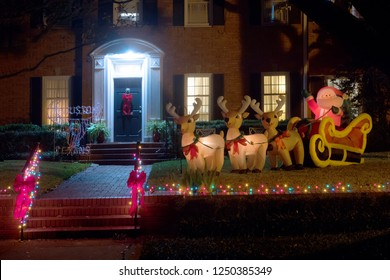 Inflatable figures: Santa Claus in a sleigh with deer near the house. Christmas decor. Winter, Night, Houston, Texas,  United States