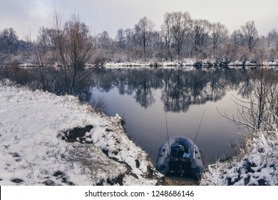 Inflatable fishing boat on the bank of a winter river.