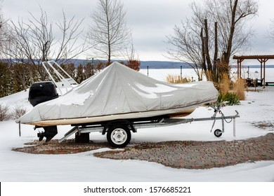 Inflatable luxury fishing motorboat wrapped in cover standing over trailer for winter period seasonal storage at backyard. Shrink-wrapped vessel winterized on parking