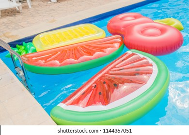inflatable mattresses in the pool in the form of watermelon, pineapple and cherry