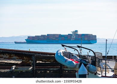 Inflatable motor boat with outboard motor on ship deck. Shipping containers stacked aboard of container vessel Maersk Line moored at port - San Francisco, CA, USA - 2019