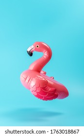 Inflatable pool toy flamingo on a blue background. Minimal summer concept.