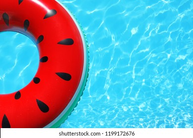 Inflatable ring floating in swimming pool on sunny day, top view with space for text