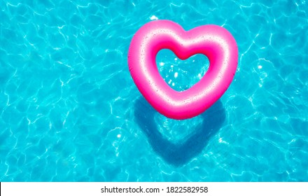 Inflatable rose heart buoy swim in the swimming pool view from above