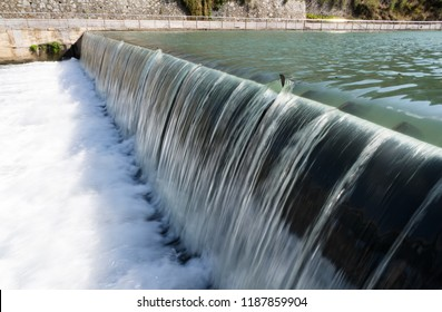 Inflatable rubber weir. Water flowing from small river dam. Irrigation development.