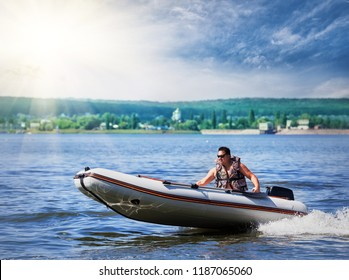 Inflatable white motor boat. A man in a life jacket and sunglasses manages an inflatable motor boat. Summer landscape. Concept of freedom and movement