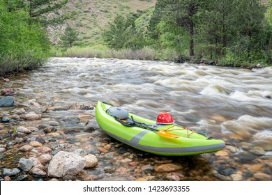 inflatable whitewater kayak on a shore of a mountain river - Poudre River in northern Colorado with highw water flow