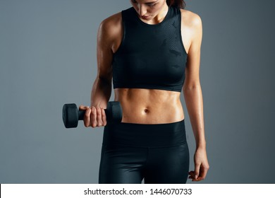 Inflated torso of a woman with dumbbells in her hand lollipops short tank top gray background cropped look