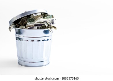 Inflation, currency waste and throwing cash away concept with picture of American 10 dollar bills in metal trash can isolated on white background with clipping path cutout and copy space