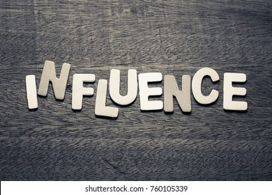 Influence word  by wood letters on wood background