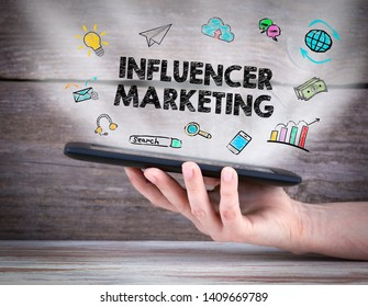 Influencer marketing concept. Tablet computer in the hand. Old wooden background