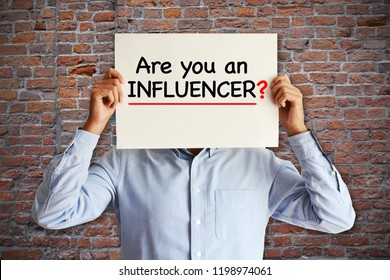 "Influencer marketing concept with ""are you an influencer"" question on white paper in young blogger's hands"