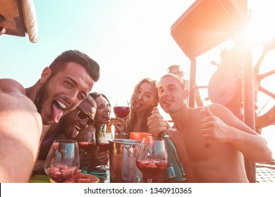 Influencer taking selfie photo with friends for making social network story during boat party - Young people drinking sangria - Technology trends, friendship and summer concept - Focus on left man