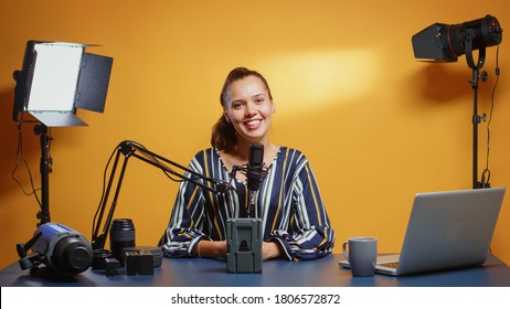 Influencer talking about professional video equipment in her studio set. Professional videography gear review by content creator new media star influencer on social media.