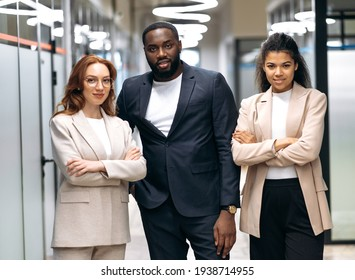 Influential business partners are confidently looking at the camera, smiling. Multiracial successful colleagues in formal stylish wear are standing in modern office, teamwork concept