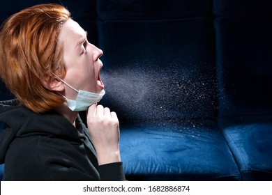 Influenza, cold, coronavirus. Infection through an airborne droplet. Girl with red hair in a medical mask coughs. A cloud of virus droplets in the air.