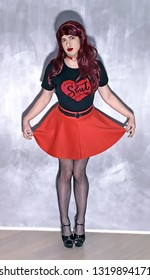 Informal crossdresser. Provacation T-shirt. Rock girl. Gothic girl. Man dressed in skirt and hells. Beautiful sensual crossdresser posing in a miniskirt. Red lips. Red choker. A woman with red hair