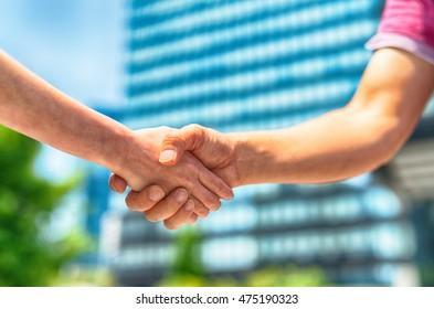 Informal handshake between man and woman.