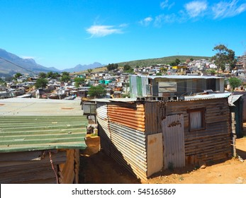 Informal settlements, huts made of metal or zinc in the Township or Cape Flats of Stellenbosch, Cape Town, South Africa with mountain and blue sky and clouds background, Slum