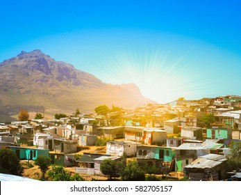 Informal settlements, huts made of metal in the Township or Cape Flats of Stellenbosch, Cape Town, South Africa with big mountain and blue sky and gold light background