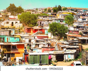 Informal settlements (Slum), huts made of metal in the Township or Cape Flats of Stellenbosch, Cape Town, South Africa with big mountain and blue sky and gold light background