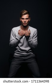 Informally ( casual ) dressed blonde young man with sharp jawline in his 20's posing in a studio in front of a black background while wearing a white sweater.