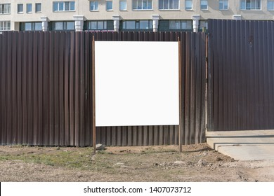 information board near the iron fence in front of the construction site, mock-up